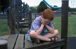 8 year old boy looking fed up - sitting crosslegged  in playground. MR