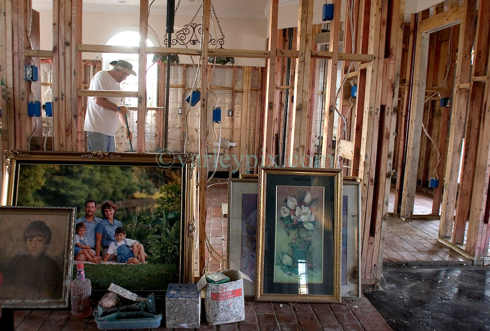 03 November, 2005. New Orleans, Louisiana. Post Katrina.<br /> Friends and family of Cory Acosta came from as far away as North carolina to help tear out sheet rock, pick up garbage and do all they can to help people rebuild their lives in Saint Bernard parish just south of New Orleans. Family portraits and treasured art work is stacked up against the gutted walls of Acosta's house. Hurricane Katrina caused a 20ft tidal surge to sweep over the land, devastating much of the parish.<br /> Photo; ©Charlie Varley/varleypix.com