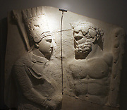 Plaster cast of upper part of a marble relief.  King Antiochus 1 of Commagene clasps the right hand of Hercules.  Cast by Hamdi-Bey, Carl Humann and Otto Puchstein in 1883 from the original at Nemrud Dagi, south-east Turkey. This is one of a series of sculptures celebrating the god-like statues of Antiochus at his tomb on Nemrud Dagi.  Elaborately dressed in Persian clothes, tiara and diadem, the king proclaims himself a friend to the Greeks and Romans in the text on the back of the original sculpture.