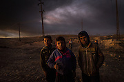 Children play near the burning oil wells in Qayyarah, set ablaze by IS militants before their retreat.<br />