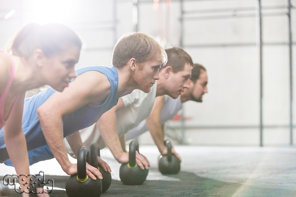 Dedicated people doing pushups with kettlebells at crossfit gym