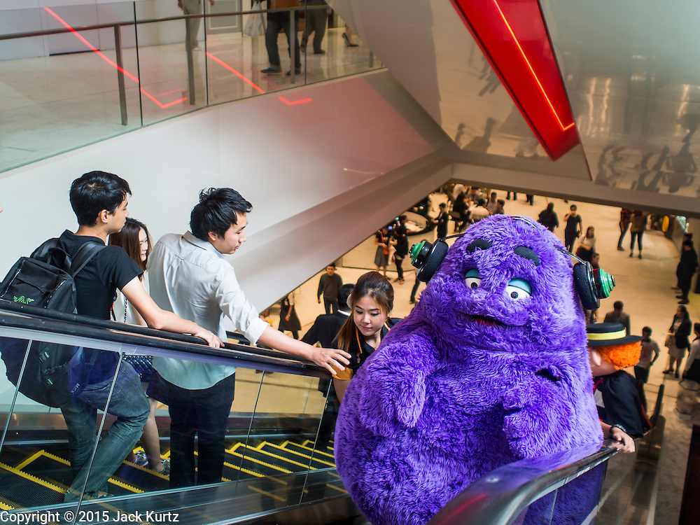 """27 MARCH 2015 - BANGKOK, THAILAND: People reach out to touch """"Grimace,"""" a fast food character used to promote McDonald's restaurants in Thailand, in """"EmQuartier,"""" a new mall in Bangkok. """"EmQuartier"""" is across Sukhumvit Rd from Emporium. Both malls have the same corporate owner, The Mall Group, which reportedly spent 20Billion Thai Baht (about $600 million US) on the new mall and renovating the existing Emporium. EmQuartier and Emporium have about 450,000 square meters of retail, several hotels, numerous restaurants, movie theaters and the largest man made waterfall in Southeast Asia. EmQuartier celebrated its grand opening Friday, March 27.   PHOTO BY JACK KURTZ"""
