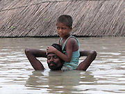 Flood victim an unidentified village farmer  carries his child through floodwaters after their house is submerged by floodwaters at sialmari village, about 329 kilometers southwest of Gauhati, the capital city of Northeastern Indian state, Assam, Monday, June 28, 2004. ..Floodwaters of the Asia'a one of the largest river, Brahmaputra and its 35 tributaries have affected more than one million in all of Indian subcontinent and disrupted communication in many parts of the India and Bangladesh, sources said. (AP Photo/ Shib Shankar Chatterjee).