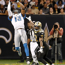 December 4, 2011; New Orleans, LA, USA; Detroit Lions wide receiver Nate Burleson (13) catches a pass over New Orleans Saints cornerback Tracy Porter (22) during the third quarter of a game at the Mercedes-Benz Superdome. The Saints defeated the Lions 31-17. Mandatory Credit: Derick E. Hingle-US PRESSWIRE