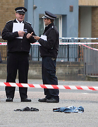 © Licensed to London News Pictures. 15/10/2015. London, UK. Police stand over HANDCUFFS and ITEMS OF CLOTHING at the scene of a shooting in Haggerston, Hackney on the corner of Lovelace Street and Haggerston Road where a police officer was shot during an armed operation. Photo credit : Vickie Flores/LNP