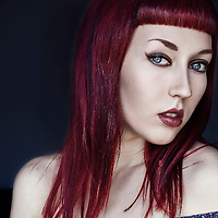 Portrait of a young female with long red hair wearing dark vampirish make up, and a blue floral blouse, with pale skin, looking into the camera, with simple interior background.