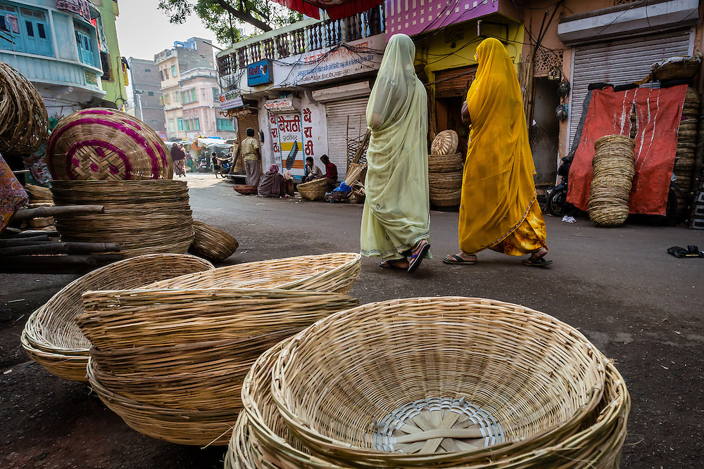 Two women walk by an area of Udaipur's street market that has mostly basket weavers