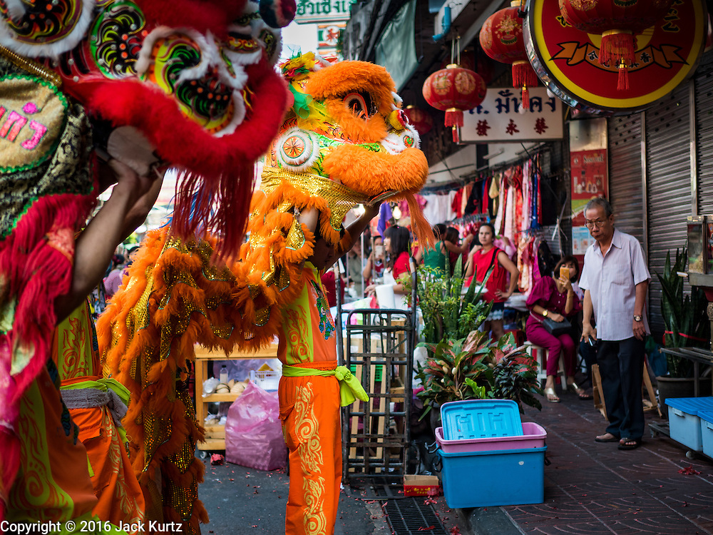 "08 FEBRUARY 2016 - BANGKOK, THAILAND: Lion dancers perform in front of a Chinese grocery for Chinese New Year on Yaowarat Road in Bangkok's Chinatown district, during the celebration of the Lunar New Year. Chinese New Year is also called Lunar New Year or Tet (in Vietnamese communities). This year is the ""Year of the Monkey."" Thailand has the largest overseas Chinese population in the world; about 14 percent of Thais are of Chinese ancestry and some Chinese holidays, especially Chinese New Year, are widely celebrated in Thailand.       PHOTO BY JACK KURTZ"