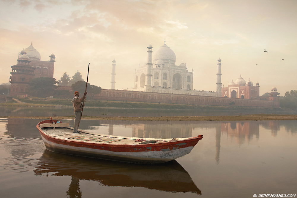 An Indian boat driver crosses the Yamuna River with the majestic Taj Mahal standing tall on the horizon. Agra, Uttar Pradesh, India.