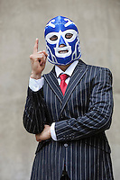 Young businessman in pinstripes suit and wrestling mask pointing up over gray background