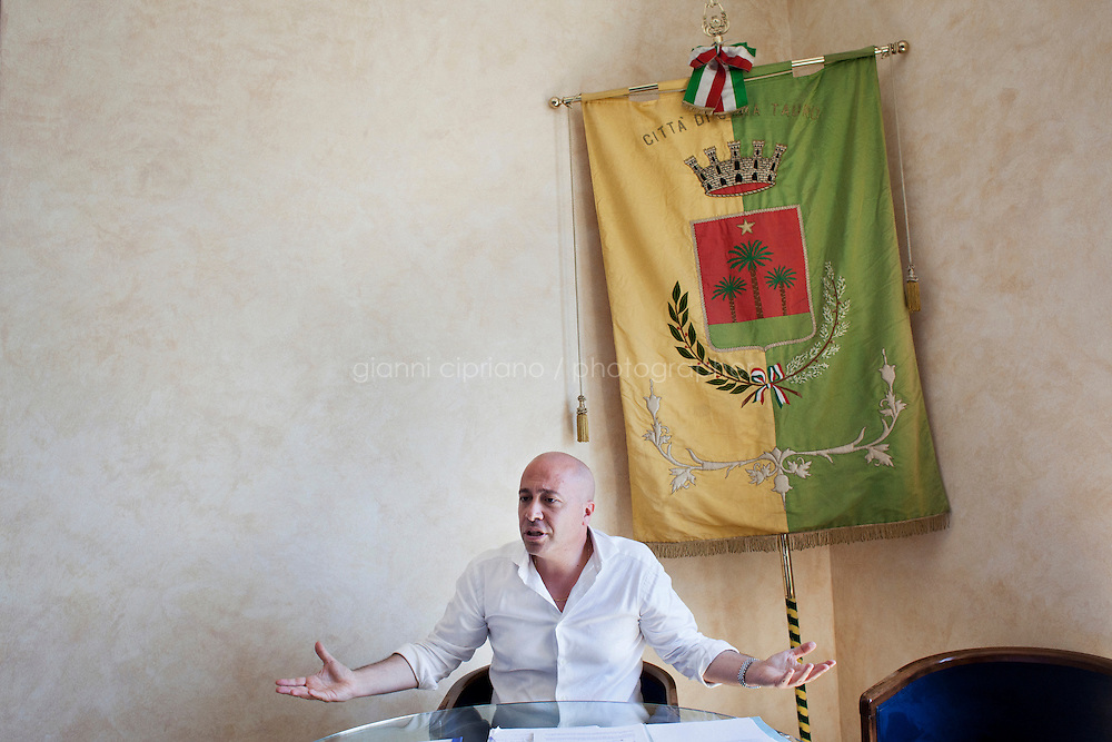Gioia Tauro, Italy - 31 August, 2012: Mayor of Gioia Tauro Renato Bellofiore, 44, complains about the debt left by his predecessors, in Gioia Tauro, Italy, on August 31, 2012. Mr Bellofiore was elected in 2010 after the former mayor and deputy mayor, Giorgio Dal Torrione and Rosario Schiavone, were arrested on Mafia charges in 2008. Both had been forced to step down when the city council was dissolved on suspicion of Mafia infiltration. Gioia Tauro is a city of 19,000 people built on an ancient Greek necrapolis and that today has the largest seaport in Italy and the sevent largest container port in Europe with its extension of 4,646 meters. Because the port is not connected to adeguate roads or rails, the ships mostly transfer containers to smaller vessels and little economic activity stays local. To authorities, the port is best known as the first point of entry for most of the cocaine that enters Europe from South America. In a routine rais earlier this month, authorities seized 176 kilos of pure cocaine with an estimated street value of 38 million euros.<br /> <br /> Calabria is one of the poorest Italian regions which suffers from lack of basic services (hospitals without proper equipment, irregular electricity and water), the product of disparate political interests vying for power. The region is dominated by the 'Ndrangheta (pronounced en-Drang-get-A), which authorities say is the most powerful in Italy because it is the welthiest and best organized.<br /> <br /> The region today has nearly 20 percent unemployment, 40 percent youth unemployment and among the lowest female unemployment and broadband Internet levels in Italy. Business suffer since poor infrastructure drives up transport costs.<br /> <br /> Last summer the European Union's anti-fraud office demanded that Italy redirect 380 million euros in structural funding away from the A3 Salerno - Reggio Calabria highway after finding widespread evidence of corruption in the bidding processes.