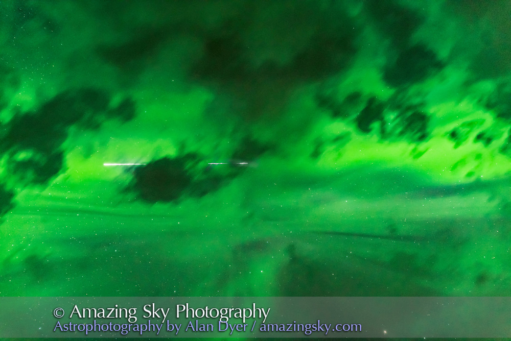 The International Space Station flying through the aurora of May 27, 2017 as the Lights converge overhead. This is looking straight up. Clouds are in the foreground, masking part of the track of the ISS. The stars of Corona Borealis are below centre.<br /> <br /> This is a stack of 2 x 6-second exposures with the 24mm Sigma Art lens at f/2.5 and Nikon D750 at ISO 2500.