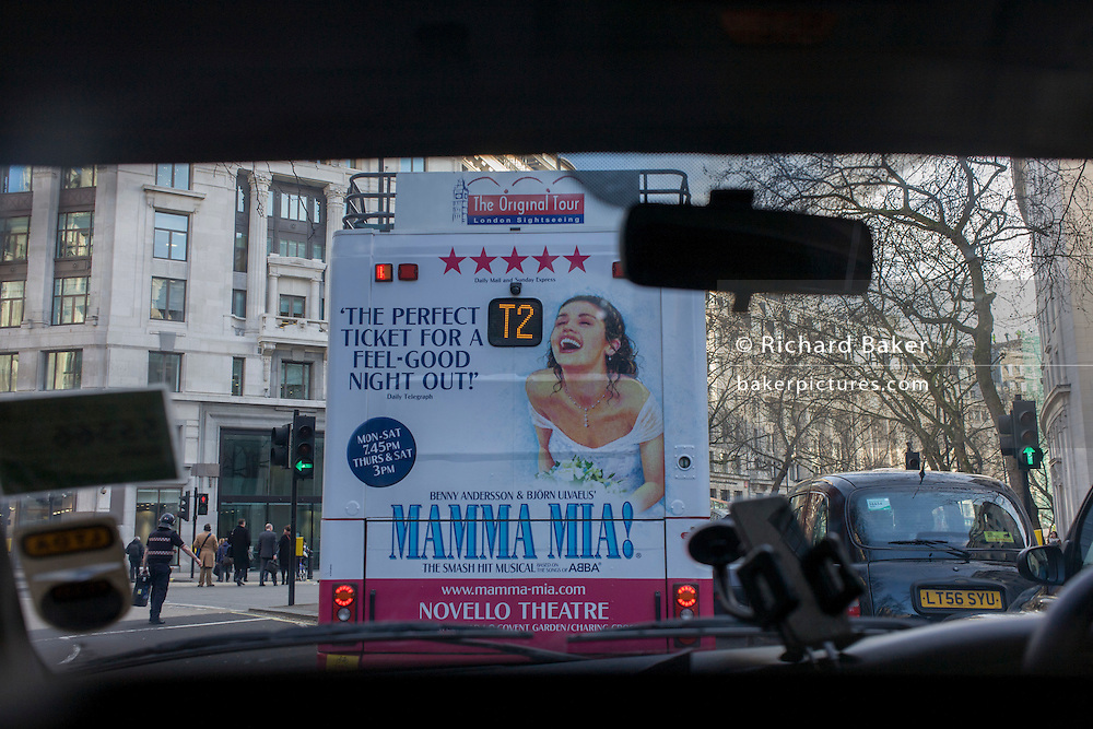 Bus rear advertising for Abba's West End musical Mamma Mia as it drives through Aldwych in central London streets.