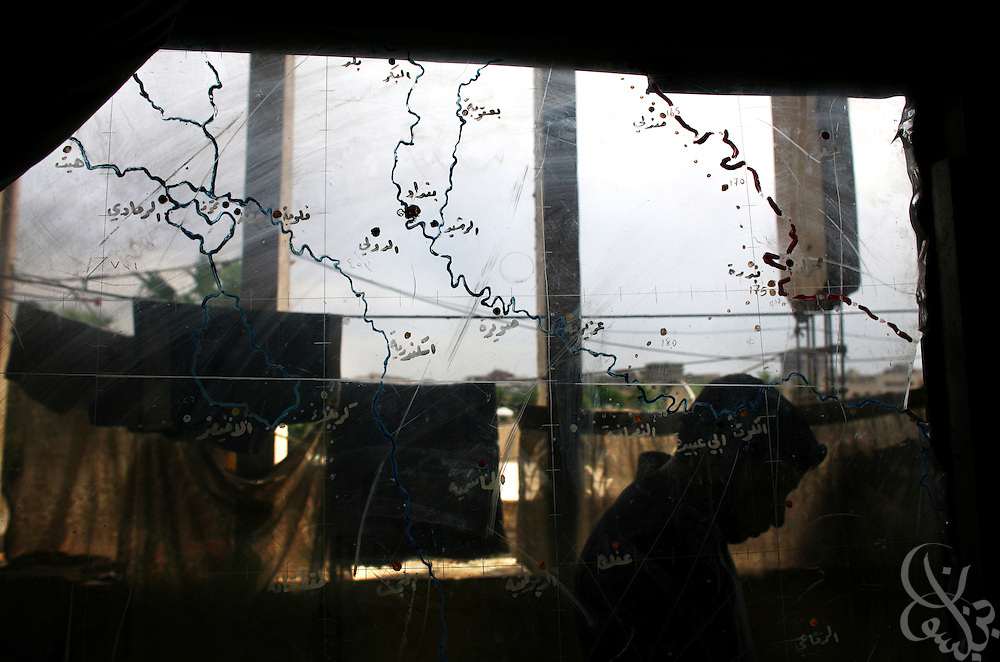 An Iraqi resident of a homeless community at the former Air Force headquarters is seen in silhouette through a scavenged air force map that has been converted into a window Oct 22, 2006 in Baghdad, Iraq. Hundreds of Iraqi families who cannot afford elevated post war housing costs have taken up residence in the abandoned air force base, making do with what they can.