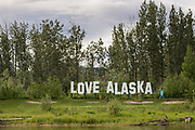 Love Alaska sign across the Chena River from Pikes Waterfront Lodge on a spring day in Fairbanks, Alaska.