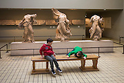 Young boys in London's British Museum play near the Ancient Greek Parthenon Metopes also knows as the Elgin Marbles. 92 Metopes were rectangular slabs placed over the columns of the Athens Parthenon temple depicting scenes from Greek mythology.
