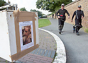 © Licensed to London News Pictures. 09/09/2014. Hanwell, UK. Divers walk past a missing person's poster of Alice Gross.  Police continue to cordon off a section of the Grand Union Canal in Isleworth in the search for missing school girl Alice Gross today 9th September 2014.  Alice Gross of Hanwell, west London, was last seen by her family at about 13:00 BST on 28 August. CCTV footage shows her walking along the Grand Union Canal tow path near the Holiday Inn at Brentford Lock between 13:30 BST and 17:30 BST.. Photo credit : Stephen Simpson/LNP