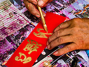 "03 FEBRUARY 2016 - BANGKOK, THAILAND:  A traditional Chinese calligrapher writes out New Year's greetings before Chinese New Year for customers on Chareon Krung Road in Bangkok's Chinatown. Thailand has the largest overseas Chinese population in the world; about 14 percent of Thais are of Chinese ancestry and some Chinese holidays, especially Chinese New Year, are widely celebrated in Thailand. Chinese New Year, also called Lunar New Year or Tet (in Vietnamese communities) starts Monday February 8. The coming year will be the ""Year of the Monkey.""            PHOTO BY JACK KURTZ"