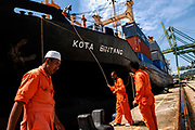 Dock workers handling a cargo ship at the deep water port. Brunei plans to develop the pot in an effort to replace its oil dependence.