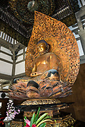 "Inside Byodo-In Temple is a statue of the Lotus Buddha, a large carved wooden image depicting Amida (or Amitabha), a celestial buddha according to the scriptures of Mahayana Buddhism. The Buddha is an original art work by Japanese sculptor Masuzo Inui. The carving was covered with cloth, painted with three coats of gold lacquer, and later coated with gold leaf. The Amida Hall (Amida-do) is also known as the Phoenix Hall (Hoo-do) because of a pair of Chinese phoenix statues on the roof. The hall and its artistry portray the culture of the Fujiwara clan's aristocracy of Japan. The peaceful Byodo-In Temple is in Valley of the Temples Memorial Park, at 47-200 Kahekili Highway, Kaneohe, on the island of Oahu, Hawaii, USA. Byodo-In Temple (""Temple of Equality"") was built in 1968 to commemorate the 100 year anniversary of the first Japanese immigrants to Hawaii. This Hawaii State Landmark is a non-practicing Buddhist temple which welcomes people of all faiths. Byodo-In Temple in O'ahu is a half-scale replica of the original Byodo-in Temple built in 1053 in Uji, Japan (a UNESCO World Heritage Site)."