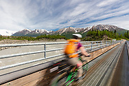 Woman riding bicycle across foot bridge to McCarthy in Wrangell-St. Elias National Park in Southcentral Alaska. Spring. Afternoon.