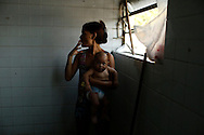 "A woman holding her baby smokes a cigarette as she waits for a washing machine, before doing laundry inside the bathroom at the Nova Tuffy slum, in an abandoned factory in Rio de Janeiro, October 17, 2014. Since seven months ago, 1,800 families have been living inside the factory, which they occupied in March, with poor sanitation services and the fear of eviction. The occupants of the factory say they are not included in the housing program ""Minha Casa, Minha Vida"" (My House, My Life), and they would like to be included by the Brazilian government. The housing program is one of several government initiatives aimed at reducing poverty and social inequality that President Dilma Rousseff has held up as achievements of her administration as she campaigns for re-election. Photo/Pilar Olivares"