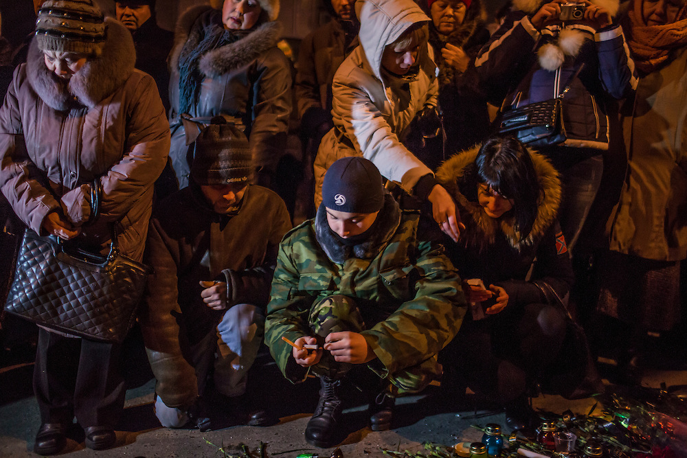 DONETSK, UKRAINE - JANUARY 24, 2015: People light candles and lay flowers at a memorial event for victims of a rocket strike that hit a trolleybus two days earlier in Donetsk, Ukraine. The attack killed at least eight civilians and injured many more. CREDIT: Brendan Hoffman for The New York Times