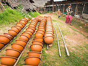 02 NOVEMBER 2014 - TWANTE, YANGON DIVISION, MYANMAR: Pottery bowls dry in the potters' village in Twante, Myanmar. Twante, about 20 miles from Yangon, is best known for its traditional pottery. The pottery makers are struggling to keep workers in their sheds though. As Myanmar opens up to outside investments and its economy expands, young people are moving to Yangon to take jobs in the better paying tourist industry or in the factories that are springing up around Yangon.    PHOTO BY JACK KURTZ