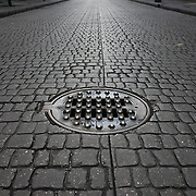 A drain and faux cobblestones on a street in the Centro Historico area of Mexico City, Mexico.