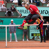 7 June 2009: An intruder on the court jumps over the net after interfering with Roger Federer of Switzerland during the Men's Singles Final match on day fifteen of the French Open at Roland Garros in Paris, France.