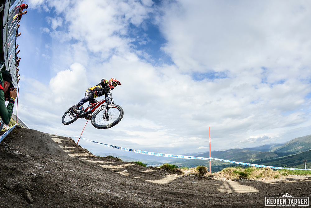 Francesco Colombo flys through the air whilst crowds watch from above at the top of the Fort WIlliam downhill track during Saturday practise at the UCI Mountain Bike World Cup.