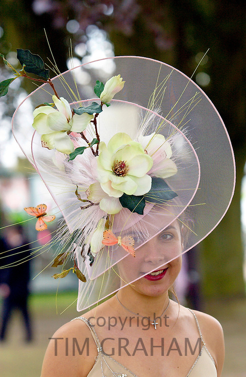 Race-goer wearing an elaborate hat with flowers and silk butterflies at Royal Ascot Races