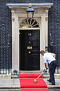 © Licensed to London News Pictures. 01/11/2012. Westminster, UK A man brushes the red carpet outside prior to the visit. British Prime Minister David Cameron welcomes The President of Indonesia, President Yudhoyono to number 10 Downing Street. Photo credit : Stephen Simpson/LNP