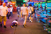 "19 JANUARY 2013 - BANGKOK, THAILAND:  A beggar crawls past tourists on Soi Cowboy, a red light district in Bangkok. Prostitution in Thailand is technically illegal, although in practice it is tolerated and partly regulated. Prostitution is practiced openly throughout the country. The number of prostitutes is difficult to determine, estimates vary widely. Since the Vietnam War, Thailand has gained international notoriety among travelers from many countries as a sex tourism destination. One estimate published in 2003 placed the trade at US$ 4.3 billion per year or about three percent of the Thai economy. It has been suggested that at least 10% of tourist dollars may be spent on the sex trade. According to a 2001 report by the World Health Organisation: ""There are between 150,000 and 200,000 sex workers (in Thailand).""       PHOTO BY JACK KURTZ"