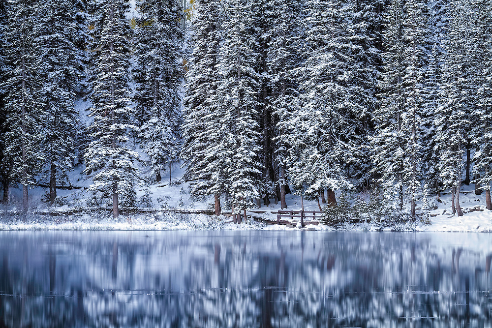 Show covered pine trees surround the simple path around a small alpine lake in Utah's Wasatch Mountains.