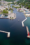 High-angle, aerial view of the Algoma Lighthouse, Algoma, Wisconsin, with a boat entering the harbor.