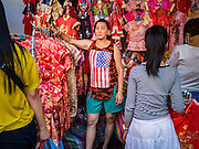 "31 JANUARY 2016 - BANGKOK, THAILAND: A woman sells new clothes for Chinese New Year at a stand on Yaowarat Road, in Bangkok's Chinatown district. Chinese New Year, also called Lunar New Year or Tet (in Vietnamese communities) starts Monday February 8. The coming year will be the ""Year of the Monkey."" Thailand has the largest overseas Chinese population in the world; about 14 percent of Thais are of Chinese ancestry and some Chinese holidays, especially Chinese New Year, are widely celebrated in Thailand.           PHOTO BY JACK KURTZ"