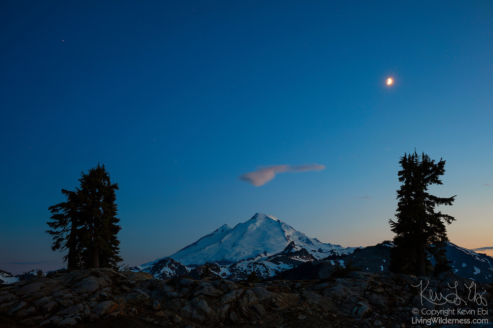 Mount Baker, a volcano located in the North Cascades of Washington state, is bathed in the blue color of twilight in this view from Artist Point. Mount Baker, at 10,781 feet (3,286 meters), is the third largest volcano in Washington state and last erupted in 1880. The crescent moon is visible high in the sky.