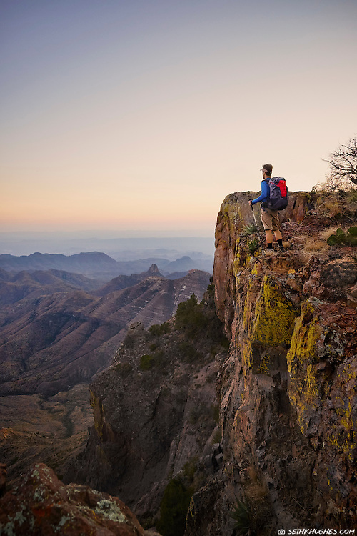 A backpacker admires the view from the South Rim, Chisos Mountains, Big Bend National Park, Texas