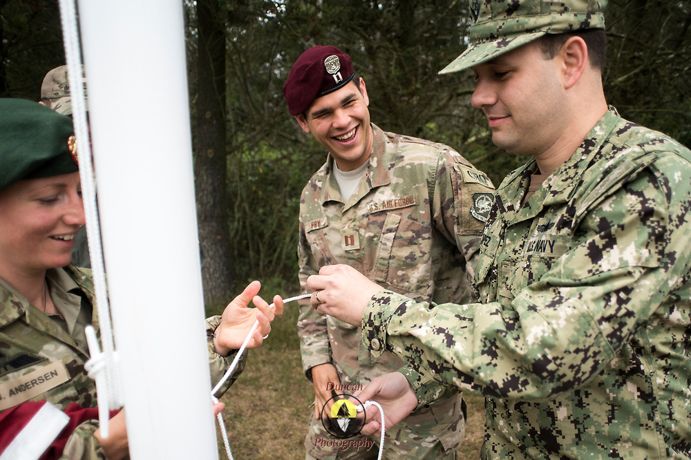 NYMINDEGAB, Denmark -- 6/29/2019 -- U.S. Navy Lt. Cmdr Ruben Lopez, right, untangles the halyard for the Danish Flag with Danish Home Guard Private Benedicta Brown as U.S. Air Force Capt Paul Fry shares a laugh.   (U.S. Navy Photo by Chief Mass Communication Specialist Roger S. Duncan)