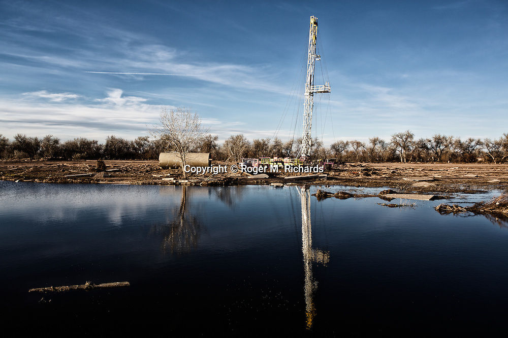 A drilling rig resumes operations beside the Platte River in Weld County, Colorado, after massive flooding caused by heavy rains caused the spill of 5,250 gallons of oil. A boom in oil and gas drilling across the American West has led to pollution and environmental problems in what were once pristine lands. Traveling rigs go from location to location, drilling down into the shale rock, and are soon followed by pumps that inject a toxic brew of water and chemicals for hydraulic extraction or 'fracking' of oil and gas. Photograph by Roger M. Richards