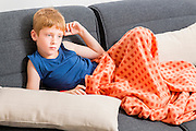 Young, sad, red haired boy of seven lounging on the sofa indoors