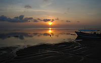 Atmospheric seashore sunset featuring a beached boat in Bali, Indonesia.