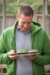 Holding a tray of microgreens
