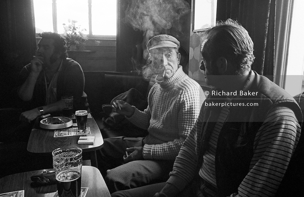 Still in the era of being able to smoke inside public places, an elderly gentleman extinguishes his match by waving it in the air to blow out the flame, exhaling and listening to a fellow-drinker in a Newport pub in south Wales. Clouds of smoke can be seen as they waft against the back light that filters through the windows of this smoky bar in the town centre. Pints of bitter are on the table in front of them and ash trays with used butts. The scene is of an industrial town's pub for working men where language is sharp and there is talk of realities of hard lives.