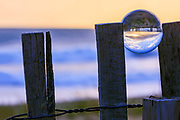 Sunrise through a crystal ball on a sand fence at the Outer Banks of North Carolina.