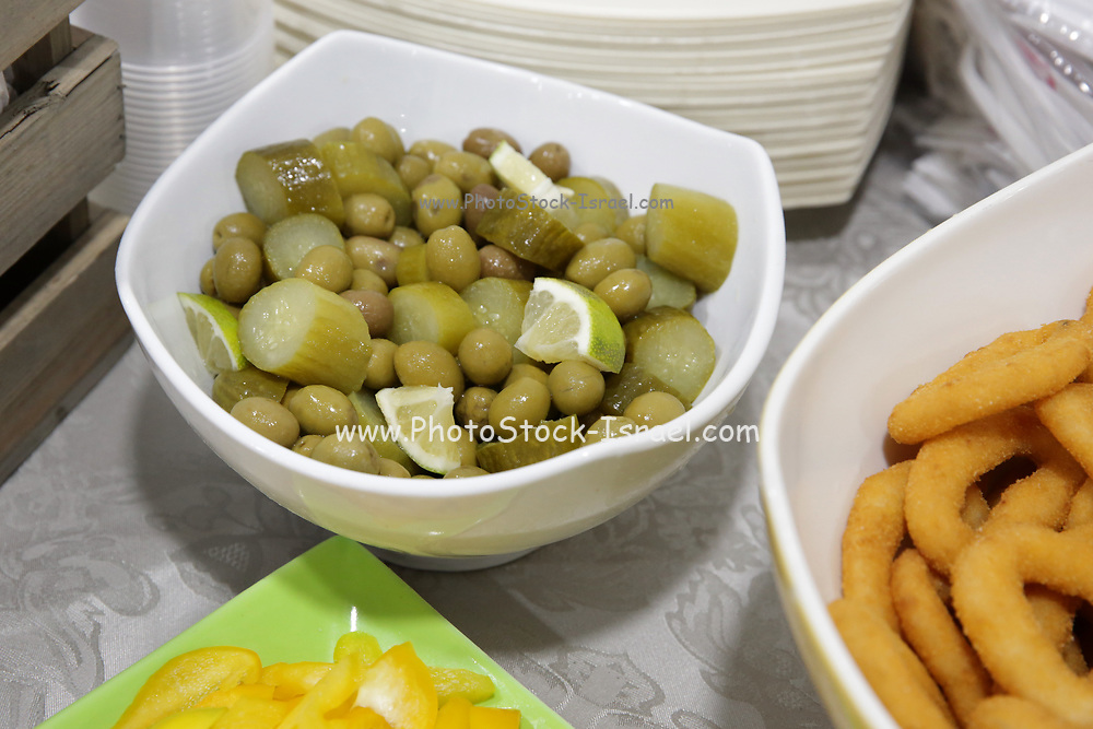 A bowl of green olives with lemon slices