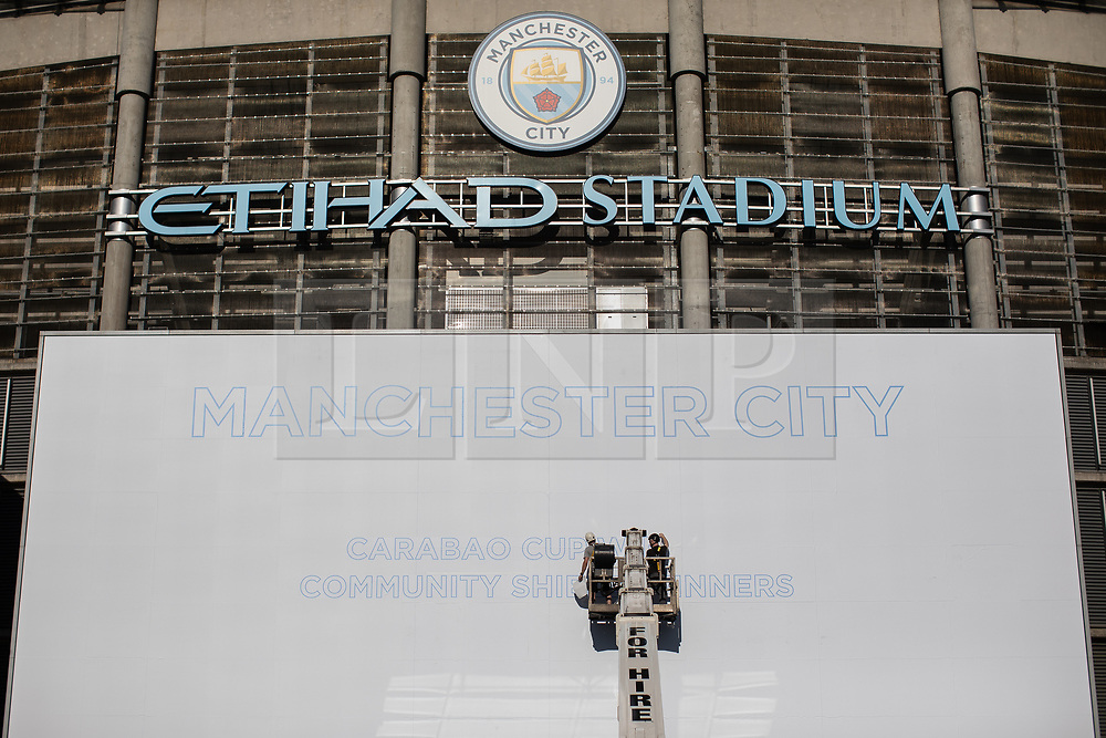 © Licensed to London News Pictures . 12/05/2019. Manchester , UK . A stage is prepared for the return of the League Trophy . Manchester City supporters celebrate after watching the club's Premier League match at Brighton on a big screen in City Square at the Etihad Stadium in which they beat Brighton and won the title for the second time in a row . Photo credit : Joel Goodman/LNP