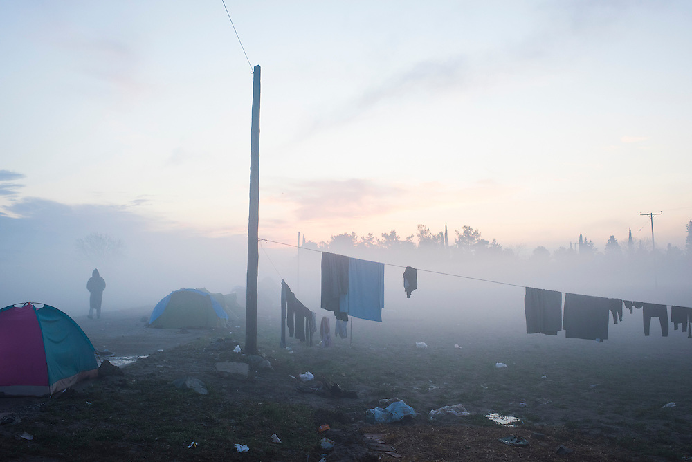 A refugee passes clothes hung out to dry at dawn in a camp on the Macedonian (FYROM) border on March 11, 2016 in Idomeni, Greece.