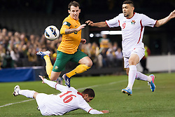 © Licensed to London News Pictures. 11/6/2013. Luke Wilkshire gets tackled during the FIFA World Cup Qualifying match between Australia Vs Jordan at Docklands stadium, Melbourne, Australia.. Photo credit : Asanka Brendon Ratnayake/LNP